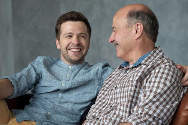O pai sênior de sorriso senta-se no bate-papo da conversa do sofá com o filho milenar passa o tempo em casa junto