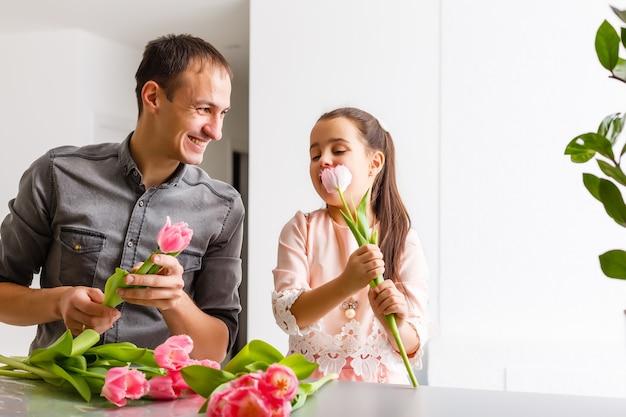 O pai tem nas mãos a menina sobre fundo claro interior. retrato de pai com flores e filha. o conceito de férias em família. dia dos pais. metade superior. fechar-se.