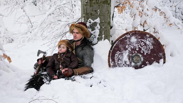 O pai viking e o filho estão sentados conversando na neve na floresta de inverno