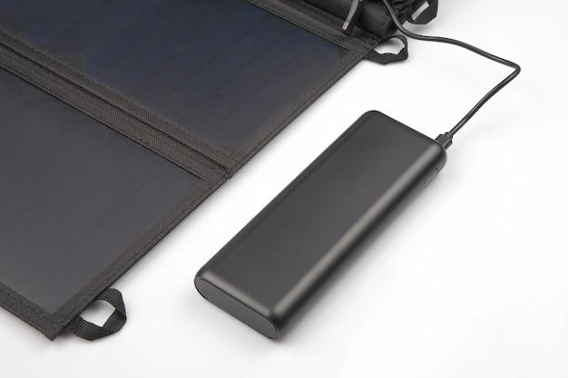 O painel solar carrega a bateria do banco de energia para o smartphone em um branco