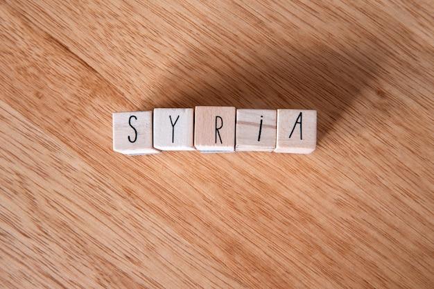 O país síria, escrito em cubos de madeira com fundo de madeira, país no oriente médio