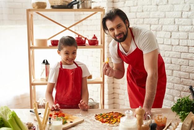 O paizinho e a filha puseram fatias da pimenta em uma pizza.