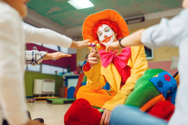 O palhaço engraçado distribui pirulitos para crianças felizes. festa de aniversário comemorando na sala de jogos, férias de bebê no playground.
