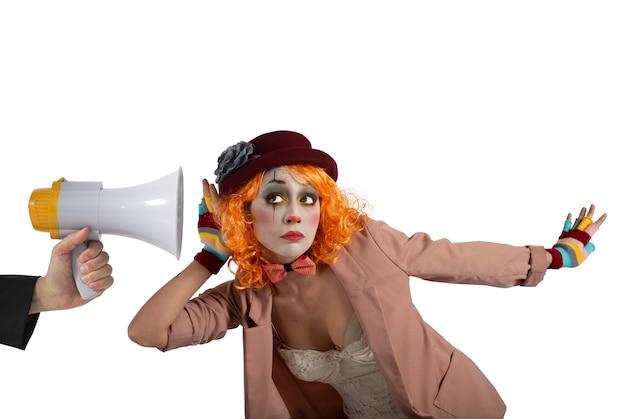 O palhaço engraçado ouve um megafone com uma mensagem importante. isolado em fundo branco