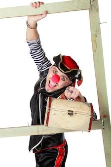 O palhaço está vestido com a roupa do pirata e segura um baú com tesouros isolados em um fundo branco