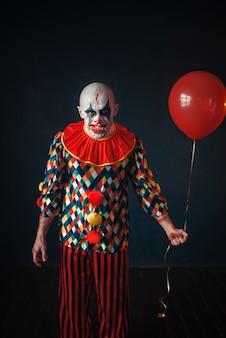 O palhaço feio e sangrento com o dedo humano nos dentes segura um balão de ar, horror. homem maquiado em fantasia de carnaval, maluco maníaco