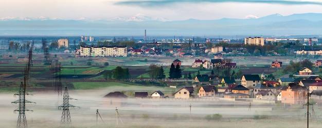 O panorama bonito das linhas elétricas de alta tensão longas da linha elétrica que esticam ao horizonte através dos campos e das árvores da mola sob a névoa densa da manhã no fundo distante da escala de montanhas carpathian.