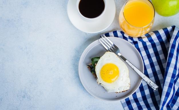 O pão de centeio brinda com espinafre e o ovo fritados na tabela azul. conceito saudável do alimento de pequeno almoço.