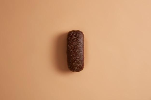 O pão de centeio recém-assado, de formato retangular decorado com cominho, preparado a partir de farinha orgânica, tem cheiro aromático, aspecto apetitoso. fundo bege. produto nutritivo. conceito de comida. postura plana