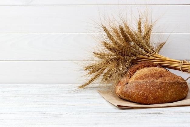 O pão e o trigo rústicos em um vintage velho planked a tabela de madeira. espaço de texto livre