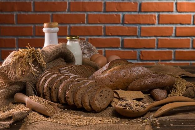 O pão integral inteiro, o leite, a farinha e o pano ensacam na tabela de madeira.