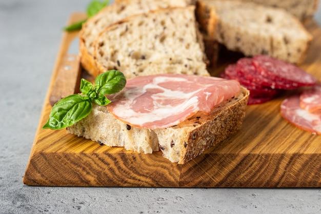 O pão tradicional do artesão com sementes e salsicha e salame de carne de porco servido em uma placa de corte de madeira. sanduíche aberto com lingüiça de porco.