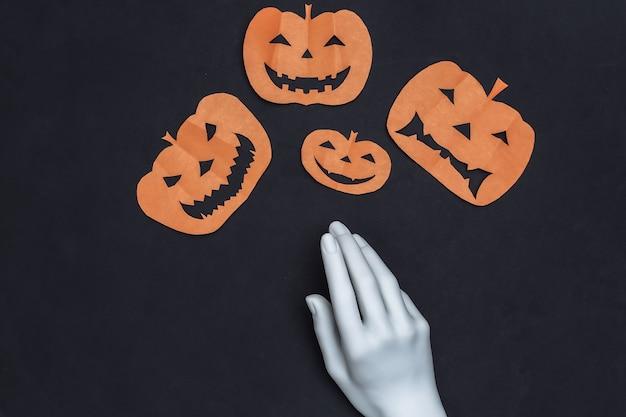 O papel artesanal cortou a abóbora de halloween e a mão do manequim em fundo preto. tema de halloween. vista do topo