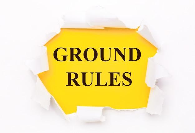 O papel branco rasgado está sobre uma superfície amarela brilhante com o texto regras fundamentais