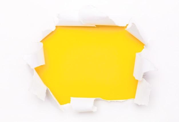 O papel branco rasgado está sobre uma superfície amarela brilhante. copie o espaço