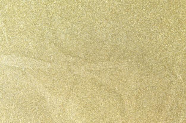 O papel brilhante do brilho dourado seja amarrotado para o fundo do natal, conceito da celebração.