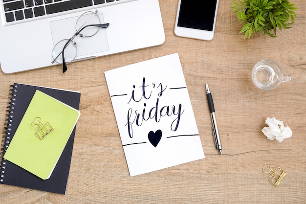 O papel com é caligrafia do texto de sexta-feira está no meio da tabela de madeira da mesa de escritório com fontes. vista superior, lay plana.
