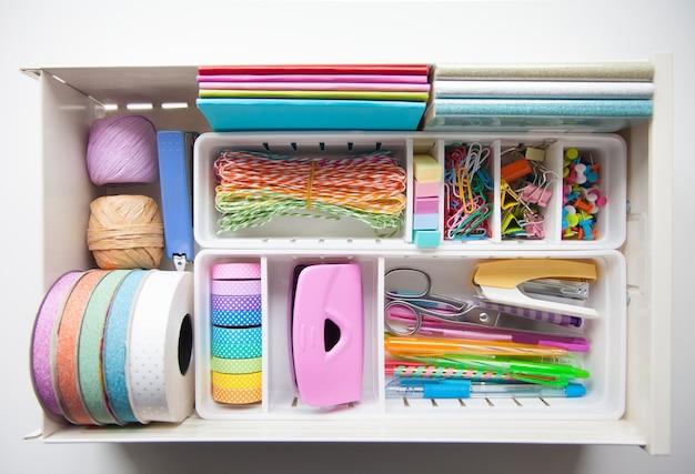 O papel de carta colorido é organizado ordenadamente em recipientes brancos nas gavetas da mesa de cabeceira. armazenamento e arrumação do local de trabalho.