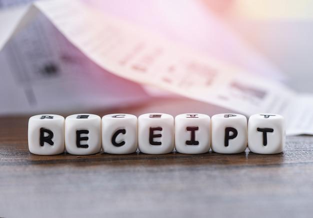 O papel do recibo no escritório da tabela com dices palavras