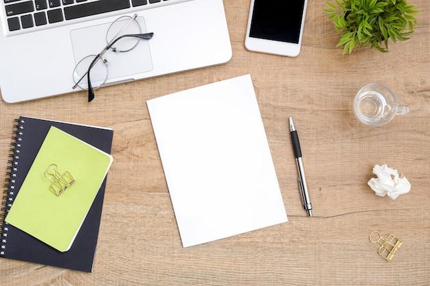 O papel em branco está sobre a tabela de madeira da mesa de escritório.