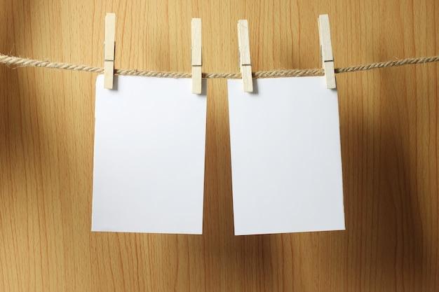 O papel vazio pendura na corda marrom com os clipes de papel de madeira no fundo de madeira.
