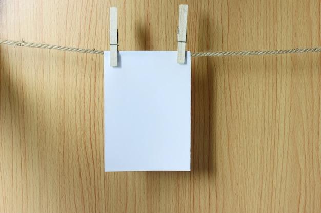 O papel vazio pendura na corda marrom com os clipes de papel de madeira.
