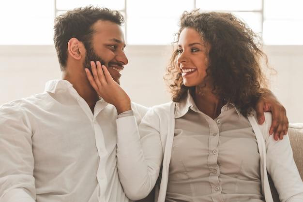 O par afro-americano bonito está abraçando e está sorrindo.