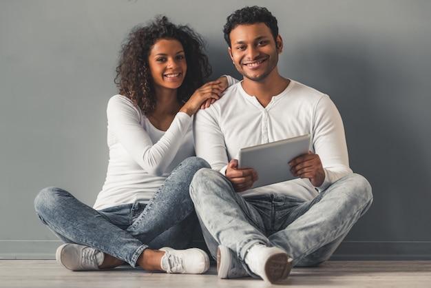 O par afro-americano bonito está usando uma tabuleta digital.