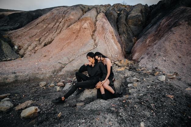 O par asiático no amor abraça o assento nas rochas. história de amor