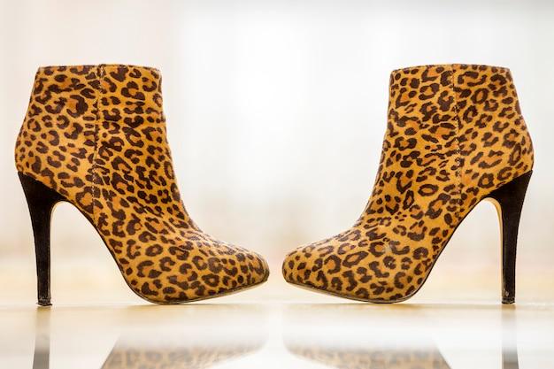 O par de mulheres amarelas do marrom do salto alto na moda calça as botas isoladas no espaço claro da cópia. estilo e moda, calçados para o outono.