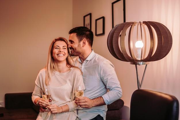 O par de sorriso aprecia passar a noite junto. beber vinho branco.