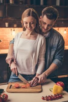O par está sorrindo ao cozinhar junto na cozinha.
