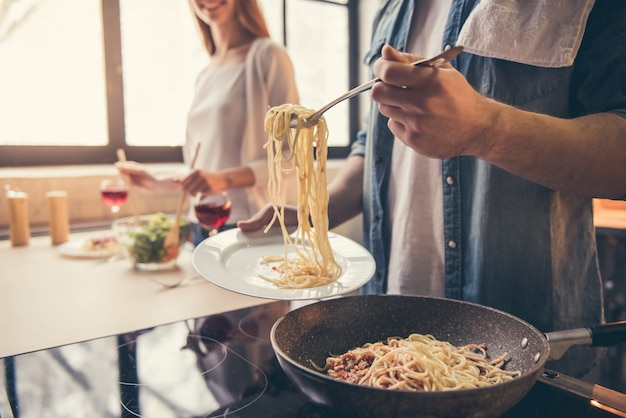O par está sorrindo ao cozinhar na cozinha.
