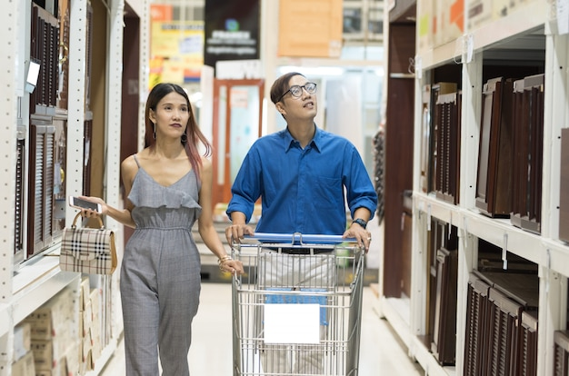 O par feliz do cliente asiático com carrinho de compras anda nas cervejas da prateleira da caixa de cartão da mobília no hipermercado.