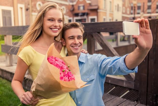 O par novo bonito está fazendo o selfie usando um telefone esperto.