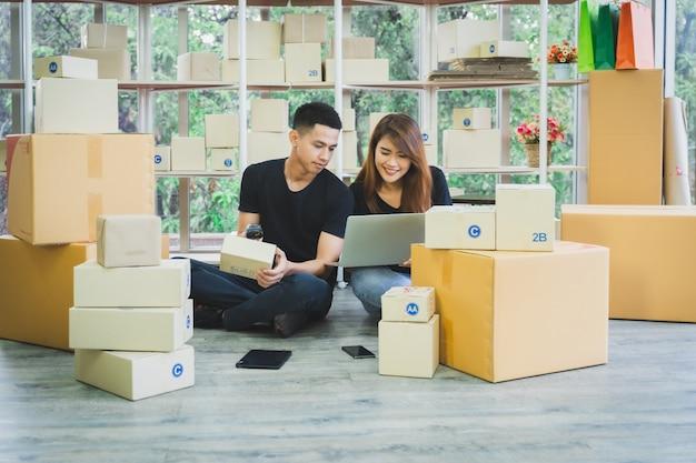 O par novo feliz do negócio asiático é trabalho junto usando o varredor do portátil e do código de barras com um empacotamento da caixa da parcela em seu escritório domiciliário da partida, vendedor do negócio em linha das pme e conceito da entrega