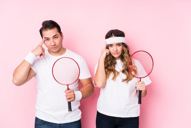 O par novo que joga o badminton isolou apontar o templo com o dedo, pensando, focalizado em uma tarefa.