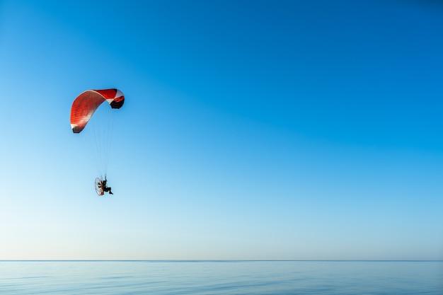 O parapente a motor sobrevoa o mar calmo e em um dia de sol claro.