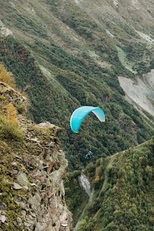 O parapente sobrevoa a montanha em um dia ensolarado. parapente nas montanhas do cáucaso