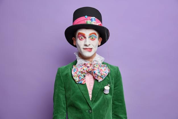 O participante do festival do desfile surpreso tem a imagem do chapeleiro do país das maravilhas usando maquiagem brilhante em poses de fantasia de carnaval contra uma parede roxa viva