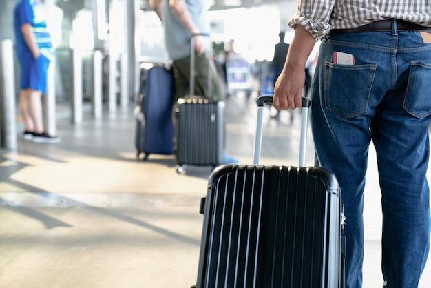 O passageiro com cartão de embarque no saco de trás e mala rolante na estação de transporte.