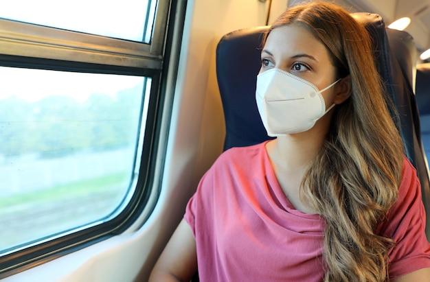 O passageiro do trem com máscara protetora viaja sentado na classe executiva, olhando pela janela