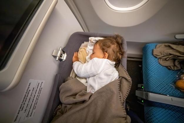 O passageiro infantil dorme com segurança e conforto no carrinho de bebê em um longo voo