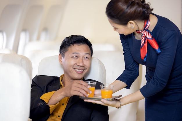 O passageiro recebe suco de laranja servido por uma aeromoça em um avião. os comissários de bordo servem a bordo