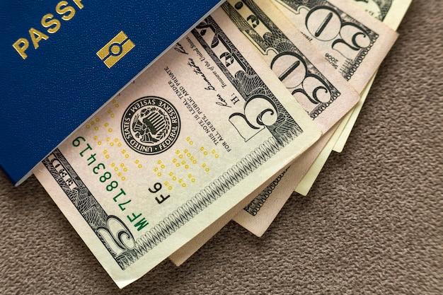 O passaporte e o dinheiro do curso, notas de cédulas dos dólares americanos na cópia espaçam o fundo, vista superior. conceito de problemas de viagem e finanças.