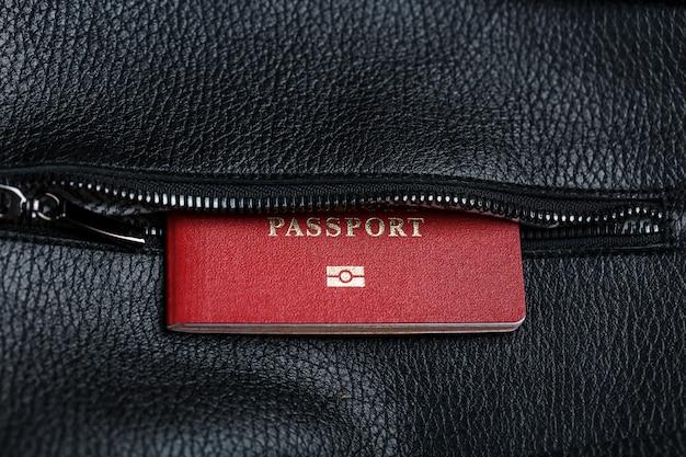 O passaporte parece fora do bolso de um close de bolsa de couro preto, macro feito à mão, materiais naturais.