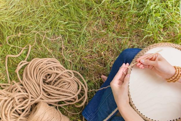 O passatempo de trabalho manual mulher está fazendo uma cesta de crochê com um cordão grosso de materiais ecológicos