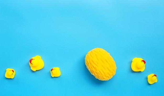 O pato amarelo brinca com a esponja amarela no fundo azul. conceito de banho de crianças.