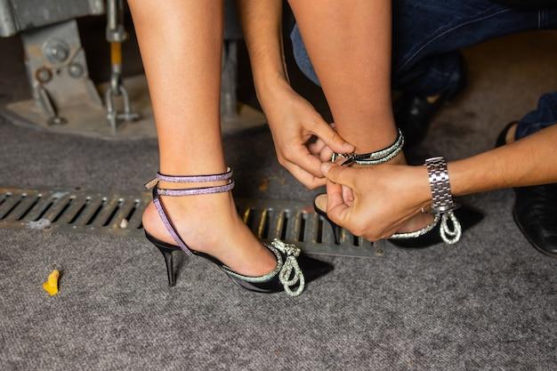 O pé de uma mulher com um sapato ficou preso no chão de madeira. buraco.