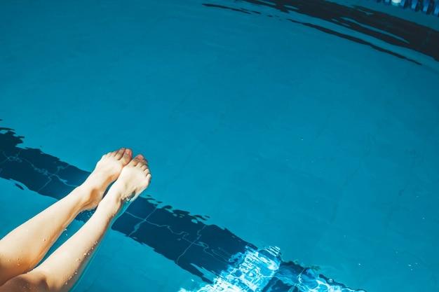 O pé do nadador é mergulhado em uma piscina de água azul transparente e clara, na qual a luz do sol brilha